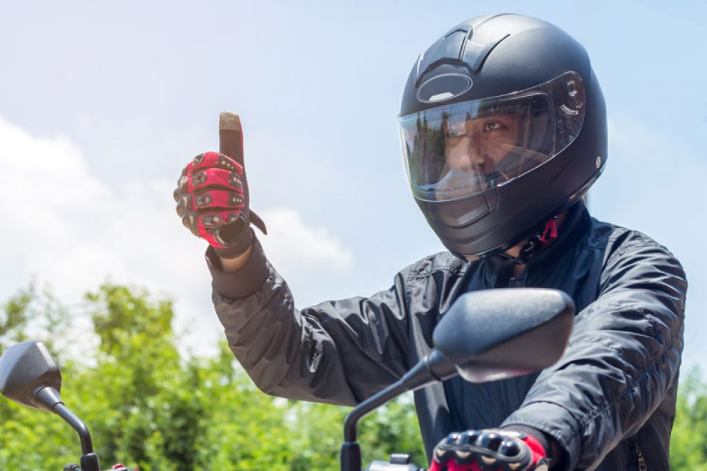 image of motorist with helmet and protective clothing