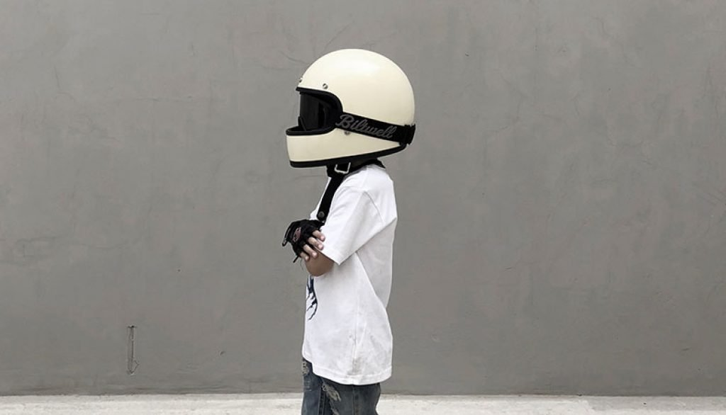 A man is posing with a huge white motorcycle helmet on his head