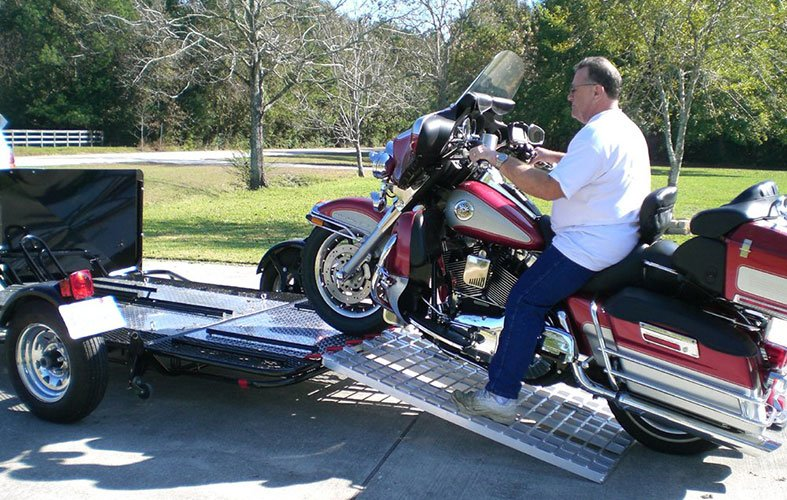 a man is pulling his motorbike-on-the motorcycle ramp