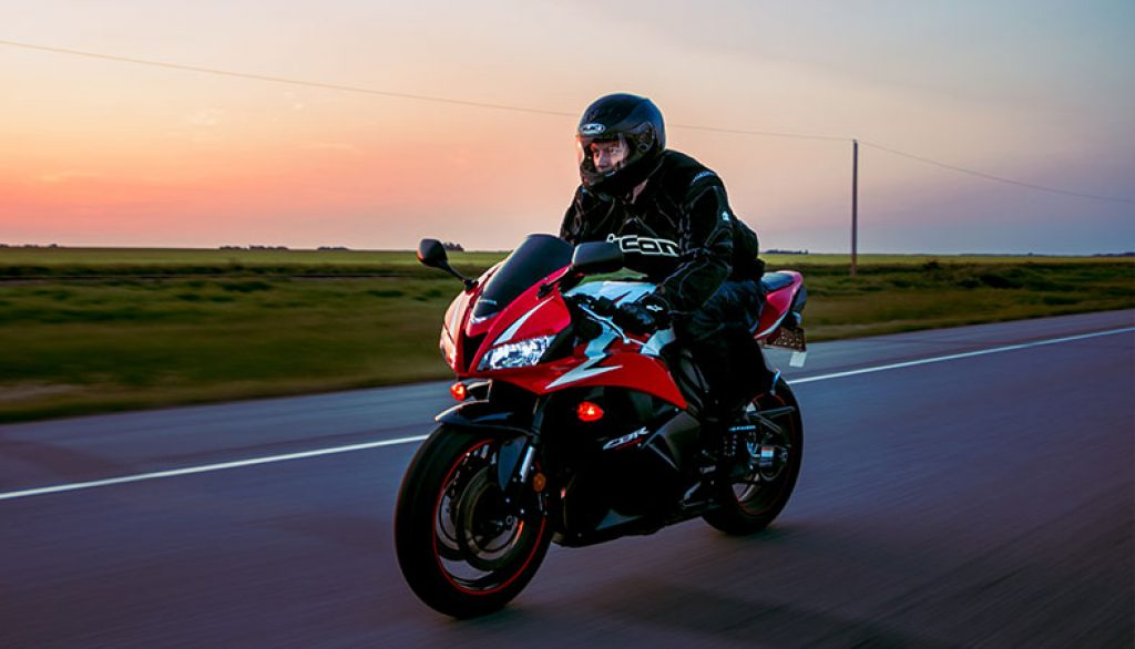a man is riding a motorcycle with a beautiful sky colors in the background