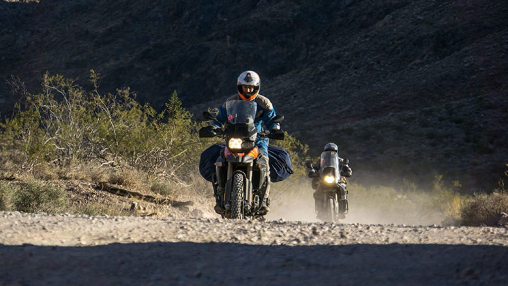 two man are riding their motorcycle