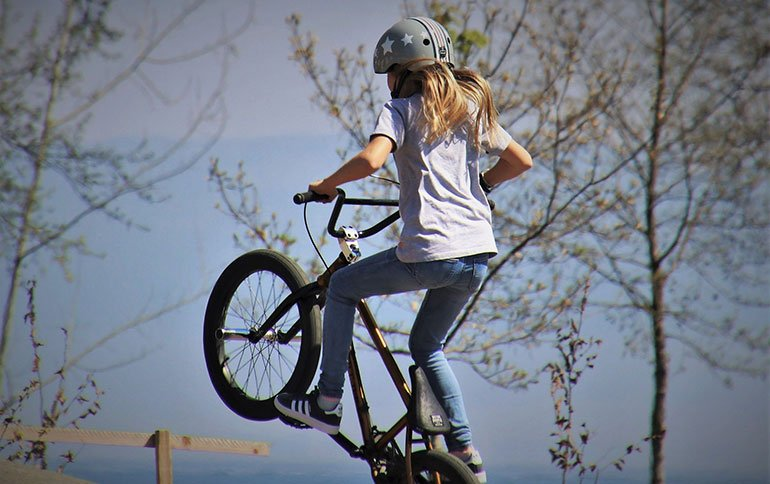 A Girl Jumping with Her BMX