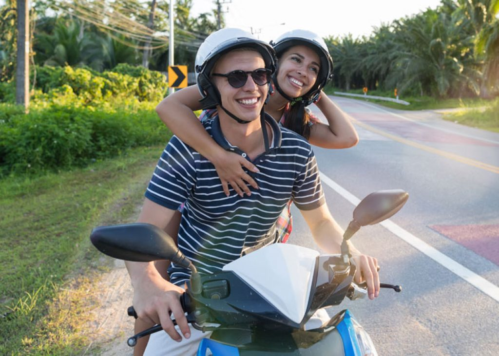 couple wearing helmets and riding a scooter