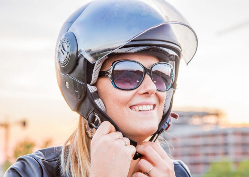 image of girl putting on scooter helmet
