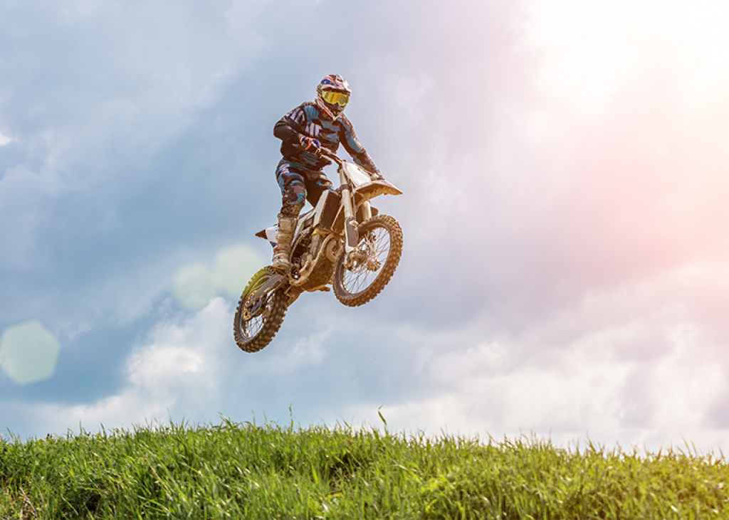 image of motorcyclist standing on dirt bike