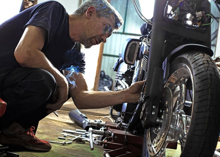 image of man with grey hair fixing motorbike