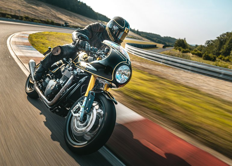 image of person in black leather riding motorcycle